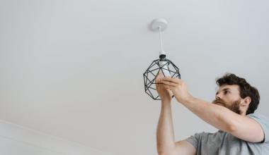 man with a beard screwing in a light bulb