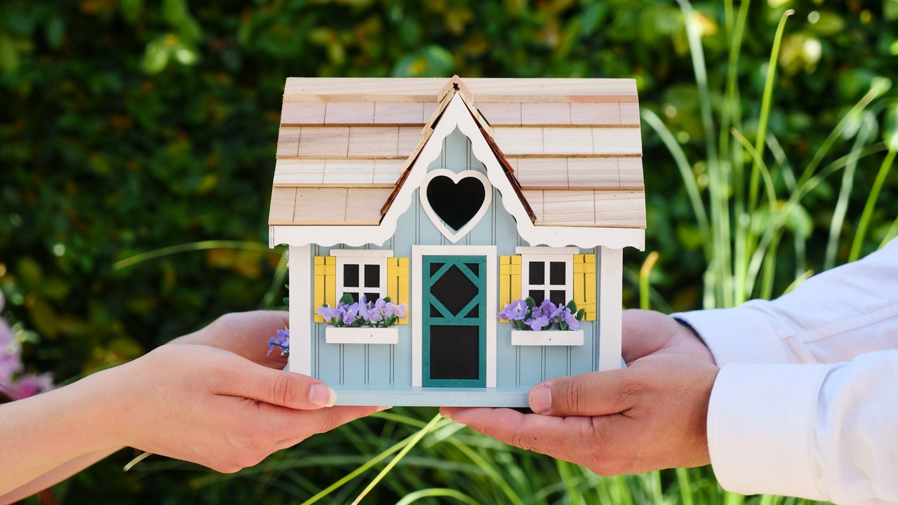 two people holding up miniature house